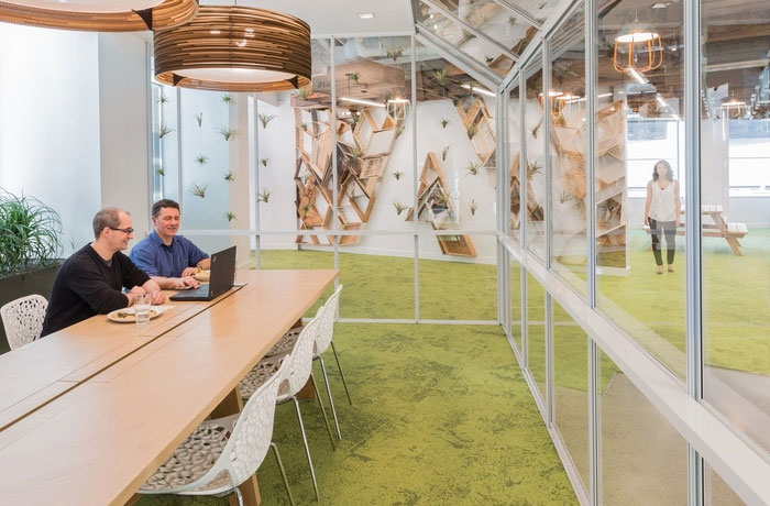 Adobe Headquarters meeting room with clear glass walls, textured grassy carpet and a long wooden table