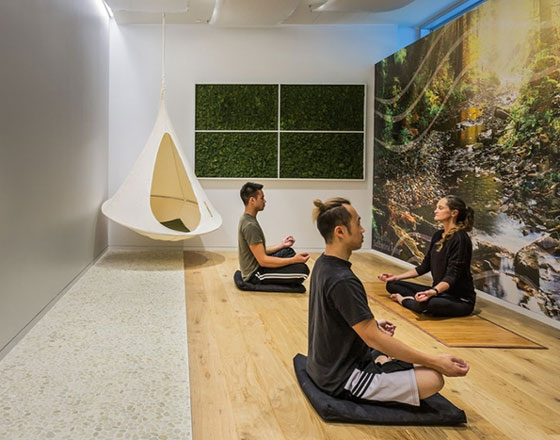 yoga room with three people and a nature mural