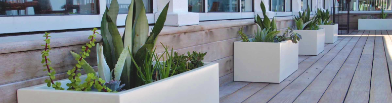A line of white rectangular fiberglass planters against a building demonstrating how to secure outdoor planters