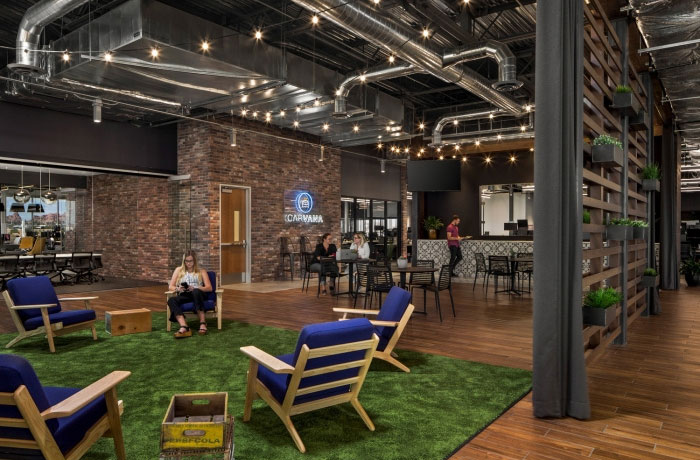 carvana office with exposed industrial ceiling, exposed brick, a green carpet to imitate grass and hanging wall plants
