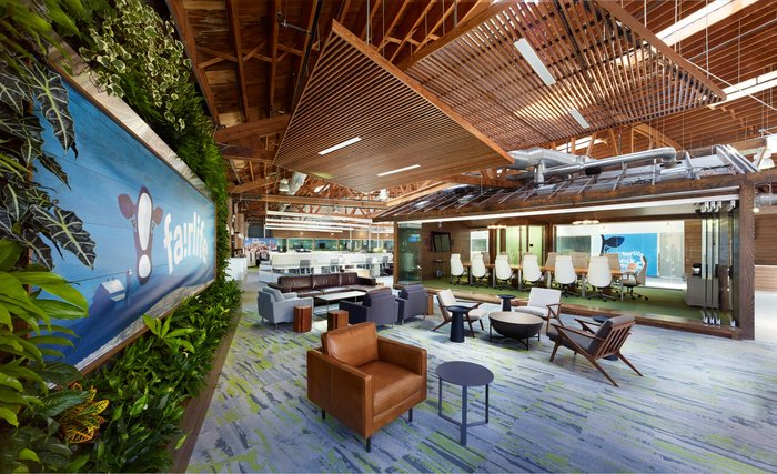 office lobby with green wall and natural wood interior showcasing biophilic design in the workplace