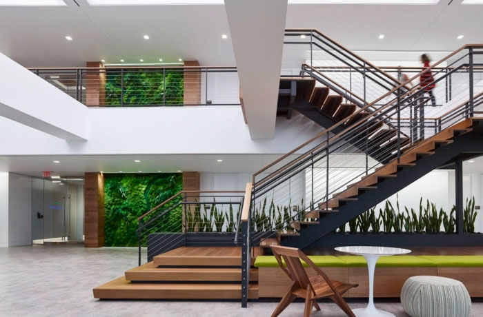 forest city office building entryway with metal and wood stairs a plant wall and a small table