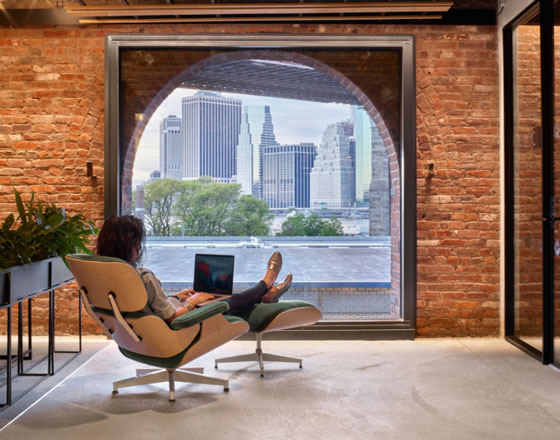 image of part of the united technologies digital office with exposed brick wall and a rounded window looking out into a city