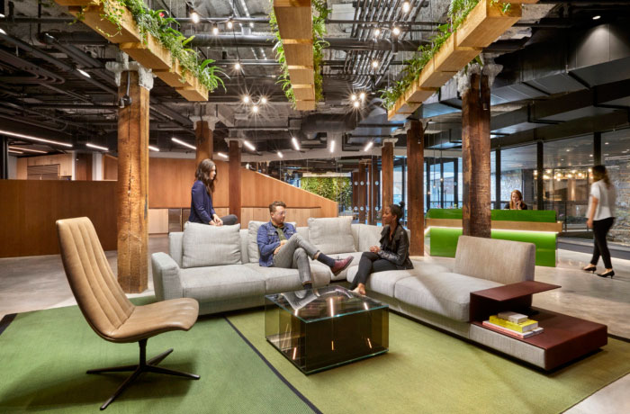 biophilic design in the united technologies workplace with neutral couches and natural wooden planters hanging from the ceiling