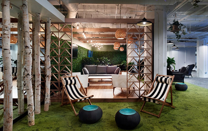 interior office with tree trunk columns, plant wall, grassy green carpet and striped folding chairs as an example of biophilic design in the workplace